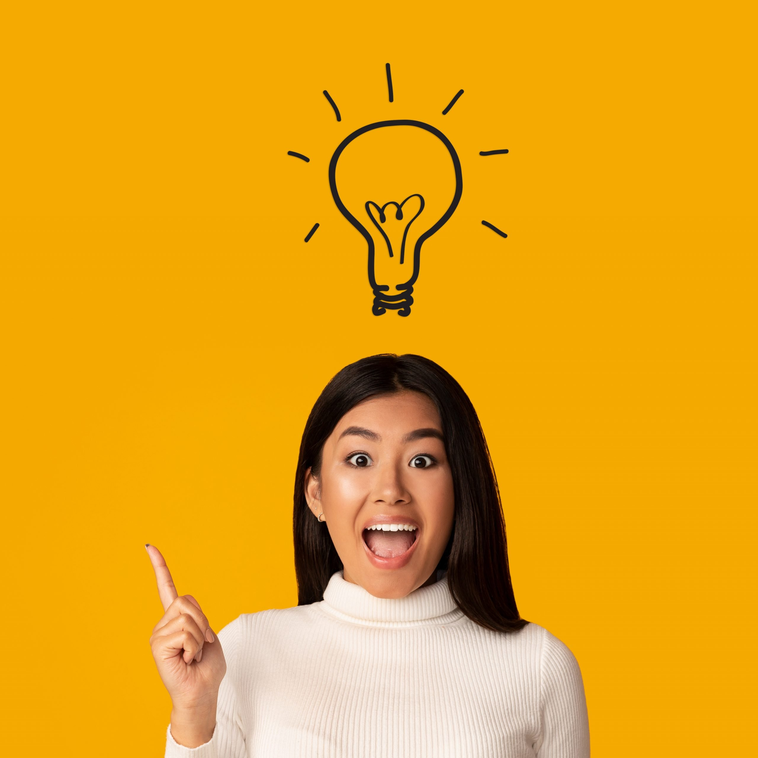Smiling, young, brown woman with idea lightbulb above her head, on a bright yellow background