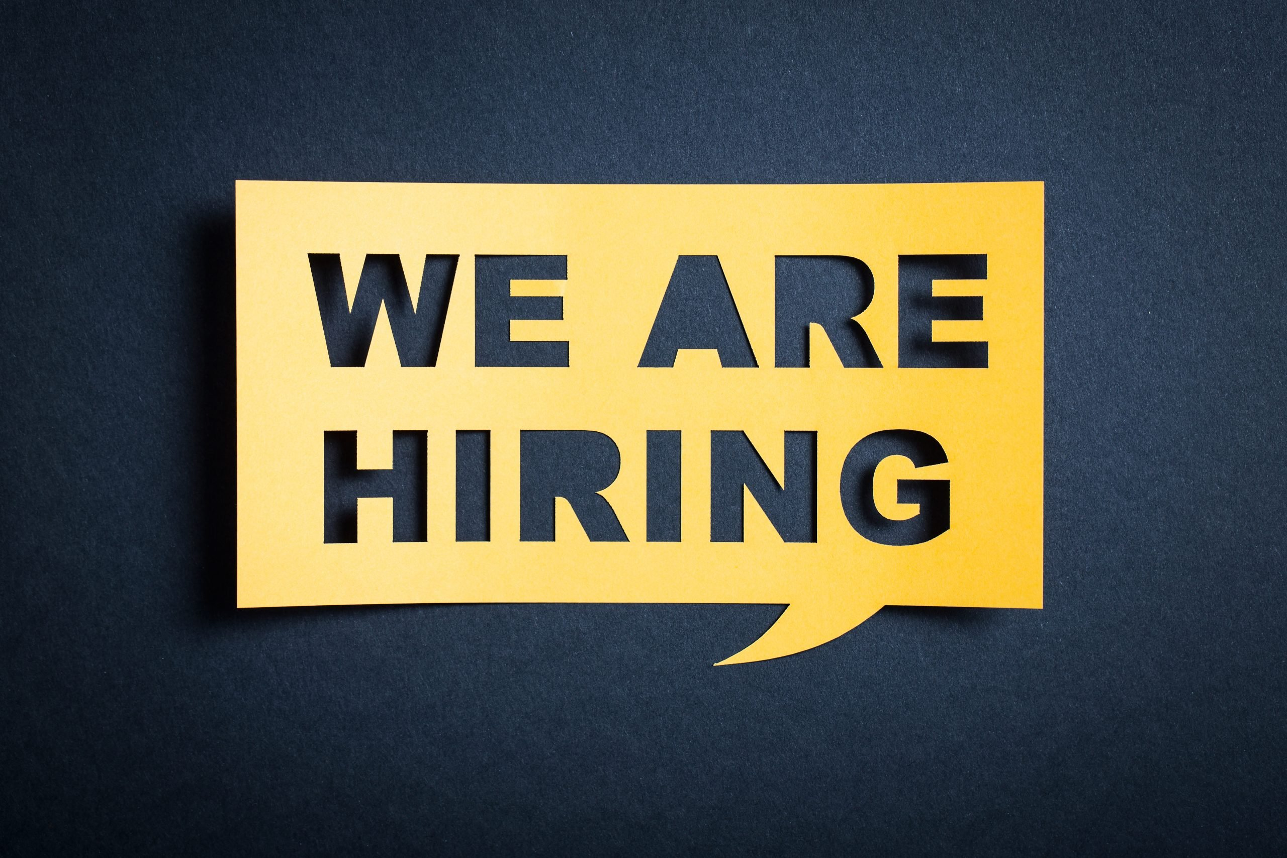 Square yellow speech bubble on a dark background saying we are hiring